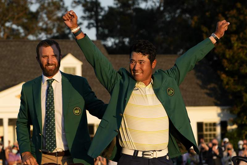 FILE - In this Sunday, April 11, 2021 file photo, Hideki Matsuyama, of Japan, puts on the champion's green jacket after winning the Masters golf tournament as Dustin Johnson watches in Augusta, Ga. (AP Photo/David J. Phillip, File)
