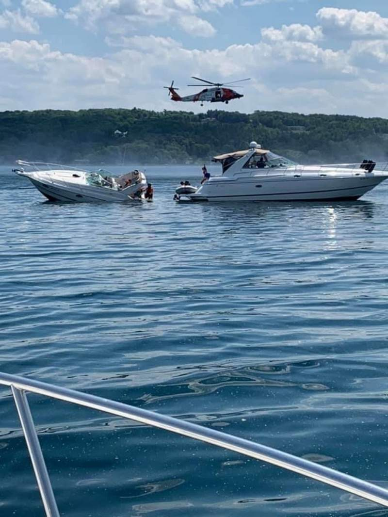 A U.S. Coast Guard rescue swimmer can be seen assisting 10 people from a sinking 30 foot vessel to a Good Samaritan's vessel in Grand Traverse Bay on Friday.