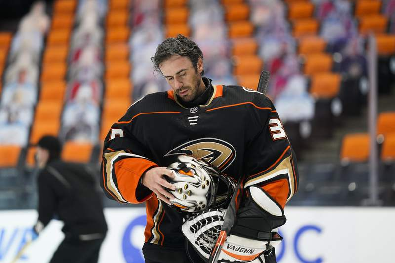 FILE - Anaheim Ducks goaltender Ryan Miller takes off his mask during the first period of an NHL hockey game against the Arizona Coyotes in Anaheim, Calif., in this Saturday, March 20, 2021, file photo. Ducks goalie Ryan Miller will retire at the conclusion of the season, ending the 18-year career of the winningest American-born goaltender in NHL history. The 40-year-old Miller announced his decision Thursday, April 29, 2021. (AP Photo/Jae C. Hong, File)