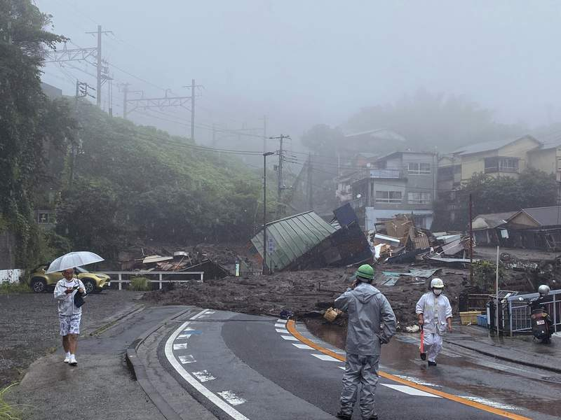 In this photo taken and provided by Satoru Watanabe, a road is covered by mud and debris following heavy rain in Atami city, Shizuoka prefecture, Saturday, July 3, 2021. A powerful mudslide carrying a deluge of black water and debris crashed into rows of houses in the same city, west of Tokyo following heavy rains on Saturday, leaving multiple people missing, officials said.(Satoru Watanabe via AP)