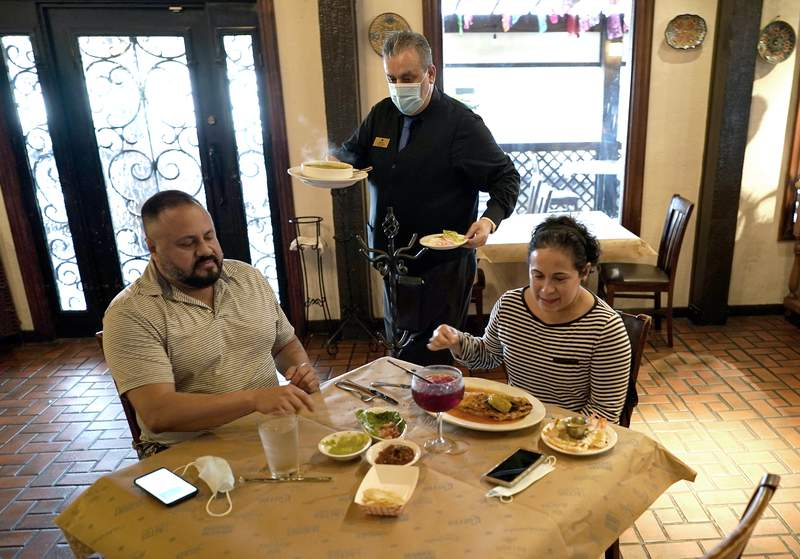 FILE - In this Wednesday, March 10, 2021 file photo, waiter Jose Bravo, center, delivers food for Alberto Castaneda, left, and his wife, Esther, at Picos restaurant in Houston. The Institute for Supply Management, an association of purchasing managers, reported Monday, April 5 that the U.S. services sector, which employs most Americans, recorded record growth in March as orders, hiring and prices all surged.  (AP Photo/David J. Phillip, File)