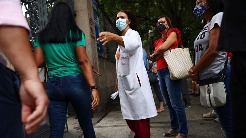 A public health worker helps people check in at a COVID-19 vaccination clinic at Museu da Republica (Museum of the Republic) on May 24, 2021 in Rio de Janeiro, Brazil. Photo by Mario Tama