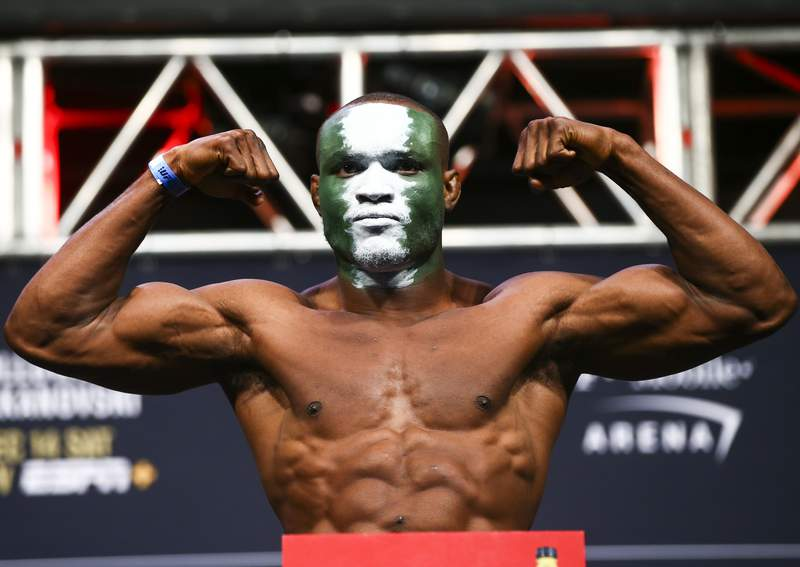 FILE - In this Dec. 13, 2019, file photo, Kamaru Usman poses during the ceremonial weigh-in event ahead of his fight against Colby Covington in UFC 245 at T-Mobile Arena in Las Vegas. The UFC revealed the location Tuesday, June 9, 2020, and announced a series of fan-free shows for Fight Island, in Abu Dhabi, starting with a card tentatively featuring three title fights at UFC 251 on July 11. The pay-per-view UFC 251 show is expected to be headlined by U.S. welterweight Kamaru Usman's title defense against Brazil's Gilbert Burns. (Chase Stevens/Las Vegas Review-Journal via AP, File)