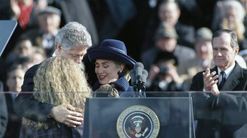 Bill Clinton receives a hug from wife, Hillary, and daughter, Chelsea, following his inauguration into the Presidency. Pictured in the background is outgoing president George H.W. Bush, who Clinton defeated in the 1992 election. (Photo by © Wally McNamee/CORBIS/Corbis