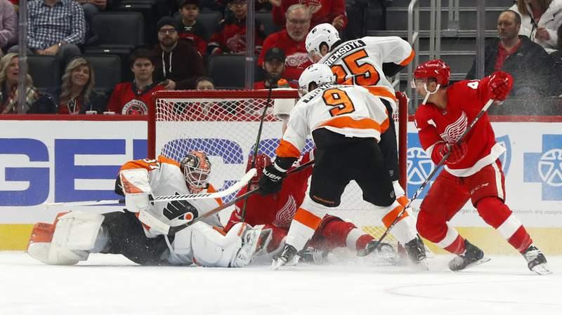 Philadelphia Flyers goaltender Brian Elliott (37) stops a Detroit Red Wings left wing Darren Helm (43) shot in the first period of an NHL hockey game Monday, Feb. 3, 2020, in Detroit.