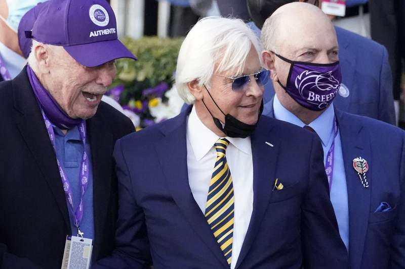File-This Nov. 7, 2020, file photo shows trainer Bob Baffert, center, and others celebrating Authentic's win in the Breeder's Cup Classic horse race at Keeneland Race Course, in Lexington, Ky. Hall of Fame trainer Baffert, who was fined and suspended last year by Arkansas racing officials for a pair of drug positives, sat through nearly nine hours of testimony Monday, April 19, 2021, on the first day of his appeal hearing.  (AP Photo/Michael Conroy, File)