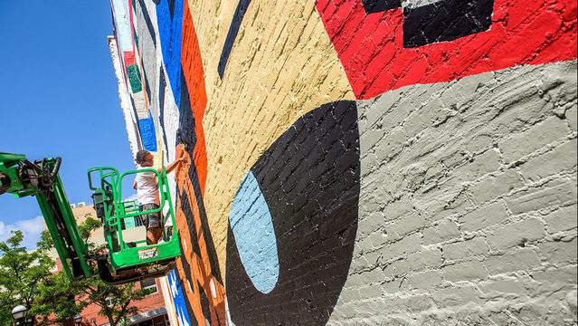 Jesse Kassel works on his mural at 120 E. Liberty Street in downtown Ann Arbor in 2019. (Ann Arbor Art Center)