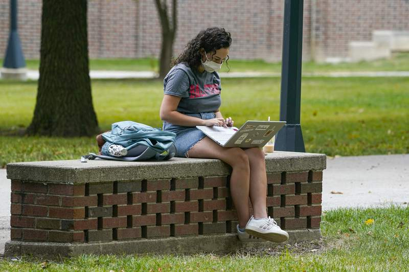 A masked student works on her laptop on the campus of Ball State University in Muncie, Ind., Thursday, Sept. 10, 2020. College towns across the U.S. have emerged as coronavirus hot spots in recent weeks as schools struggle to contain the virus. (AP Photo/Michael Conroy)