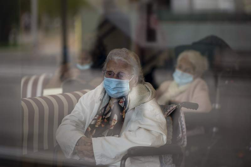 Residents look at the street through a window at the Icaria nursing home in Barcelona, Spain, Wednesday, Nov. 25, 2020.  (AP Photo/Emilio Morenatti)