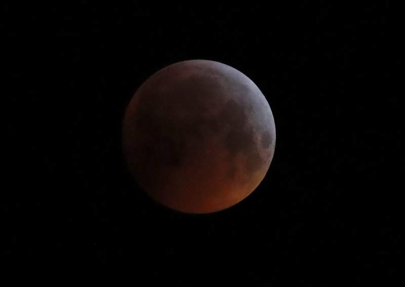 FILE - In this Monday, Jan. 21, 2019 file photo, the Earth's shadow falls across the full moon seen above Brighton, southeast England. The first total lunar eclipse in more than two years coincides with a supermoon this week for a cosmic show. This super blood moon will be visible Wednesday, May 26, 2021 across the Pacific _ offering the best viewing _ as well as the western half of North America, bottom of South America and eastern Asia. (AP Photo/Alastair Grant, File)