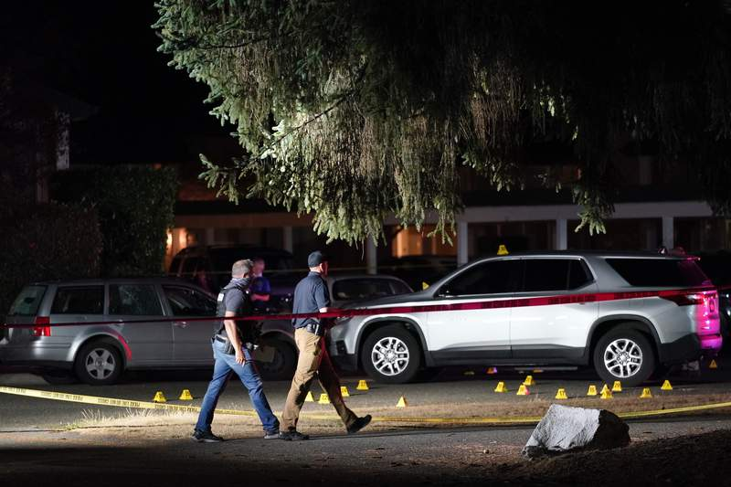 FILE - In this Sept. 3, 2020, file photo, police walk past evidence markers at a scene in Lacey, Wash., where a man suspected of fatally shooting a supporter of a right-wing group in Portland, Ore., was killed as investigators moved in to arrest him. A Washington state prosecutor has decided not to file criminal charges against police who shot and killed an antifascist fugitive wanted in the highly publicized death last year of a right-wing demonstrator in Portland, Ore., last year. A U.S. Marshals-led task force was trying to arrest Michael Reinoehl, 48, at an apartment complex in Lacey, near Olympia, in September 2020 when four officers fired at him as he exited his car. (AP Photo/Ted Warren, File)
