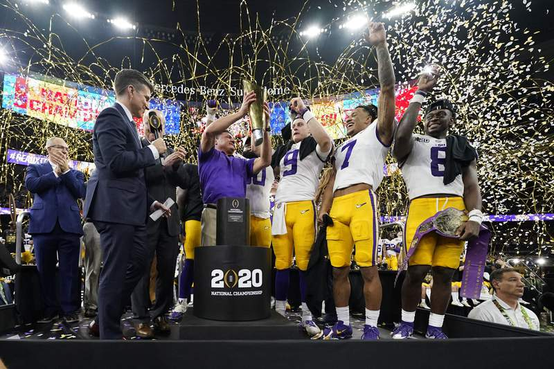 FILE - In this Jan. 13, 2020, file photo, LSU head coach Ed Orgeron holds the trophy after the team's victory over Clemson in an NCAA College Football Playoff national championship game in New Orleans. LSU has begun asking a number of football players to self-quarantine in the past week because of instances in which some players tested positive for COVID-19 after social interactions outside of the Tigers training facility. (AP Photo/David J. Phillip, File)