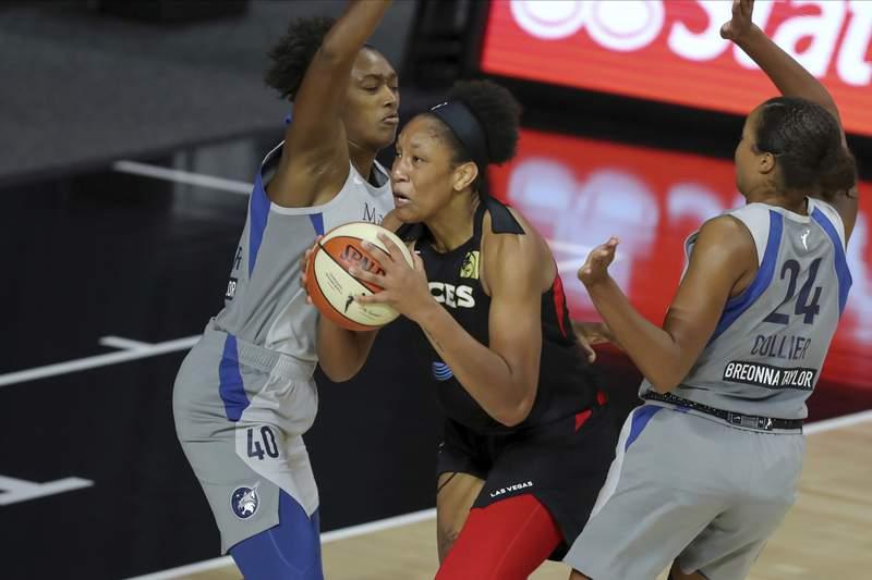 Las Vegas Aces' A'ja Wilson drives between Minnesota Lynx's Kayla Alexander (40) and Napheesa Collier during the first half of a WNBA basketball game Thursday, Aug. 13, 2020, in Bradenton, Fla. (AP Photo/Mike Carlson)