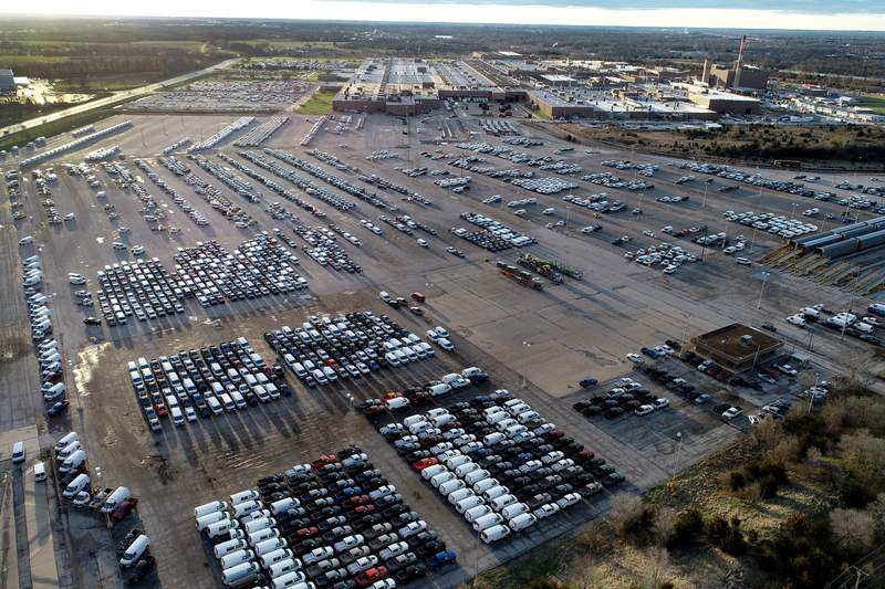 In this aerial photo, a General Motors assembly plant is seen at top right while mid-sized pickup trucks and full-size vans currently produced at the plant are seen in a parking lot outside Wednesday, March 24, 2021, in Wentzville, Mo.    The Commerce Department reported Thursday, May 27,  that orders for factory goods meant to last at least three years fell 1.3% in April after rising 1.3% in March. Transportation orders skidded 6.7%. Excluding transportation, which can be volatile from month to month, durable goods orders were up 1% in April.  (AP Photo/Jeff Roberson)