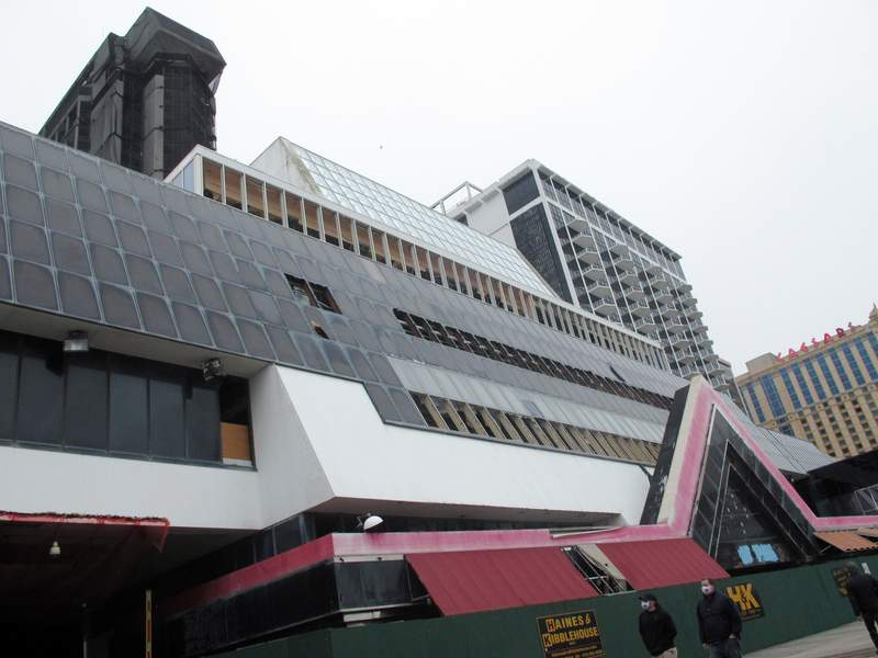 This Feb. 16, 2021 photo shows the former Trump Plaza casino in Atlantic City, N.J. on the day before its main tower, in background, was to be imploded. The casino built by former President Donald Trump was once the playground of the rich and famous, but fell into disrepair after shutting down in 2014. (AP Photo/Wayne Parry)