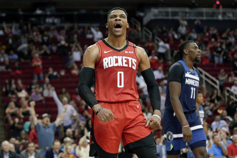 Houston Rockets guard Russell Westbrook (0) reacts after a dunk, next to Minnesota Timberwolves center Naz Reid (11) during the second half of an NBA basketball game Tuesday, March 10, 2020, in Houston. (AP Photo/Michael Wyke)