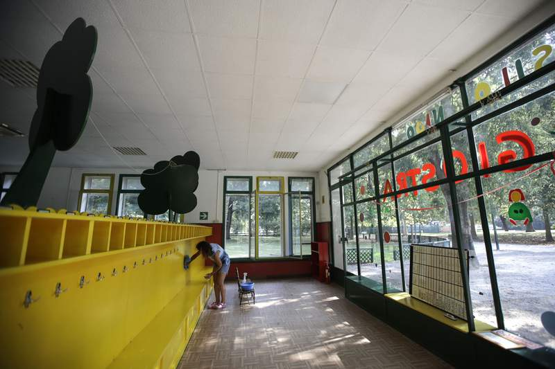 A worker cleans the coat rack in the 'La Giostra Nel Parco' (Merry go around in the park) nursery school in Milan, northern Italy, Thursday, Aug. 27, 2020, ahead of reopening. Despite a spike in coronavirus infections, authorities in Europe are determined to send children back to school. Italy, Europes first virus hot spot, is hiring 40,000 more temporary teachers and ordering extra desks, but some wont be ready until October. (AP Photo/Luca Bruno)