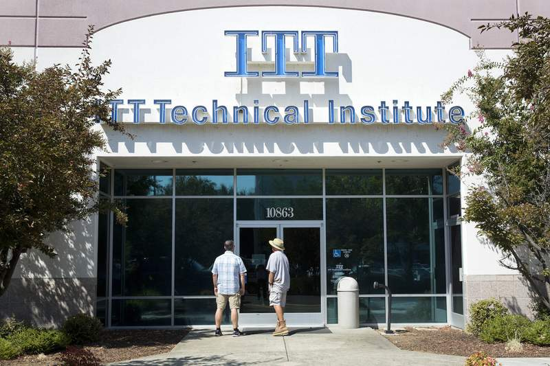 FILE - Students find the doors locked to the ITT Technical Institute campus in Rancho Cordova, Calif. The U.S. Education Department says it's erasing student debt for thousands of borrowers who attended a for-profit college chain that made exaggerated claims about its graduates' success in finding jobs. The Biden administration is approving 18,000 loan forgiveness claims from former students of ITT Technical Institute, a chain that closed in 2016. (AP Photo/Rich Pedroncelli, File)
