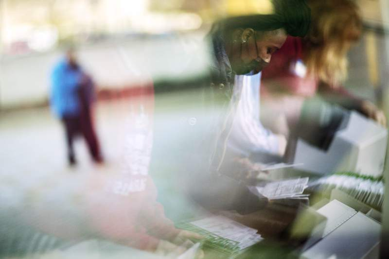 FILE - In this Nov. 3, 2020, file photo, election inspectors are reflected in a window at right as they begin processing ballots while a voter outside arrives to drop a ballot into an official box on Election Day at City Hall in Warren, Mich. (AP Photo/David Goldman, File)