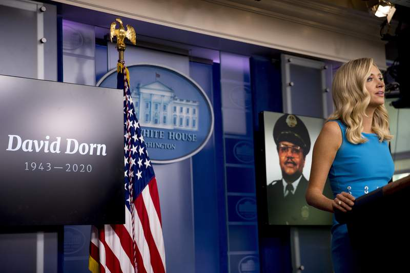 FILE - In this June 3, 2020, file photo a photograph of retired St. Louis police captain David Dorn who was shot and killed while guarding a pawn shop from a looter is displayed behind White House press secretary Kayleigh McEnany as she speaks during a briefing at the White House in Washington. Ann Marie Dorn, the widow of David Dorn, will speak Thursday, Aug. 26, as part of the Republican National Convention. (AP Photo/Andrew Harnik, File)