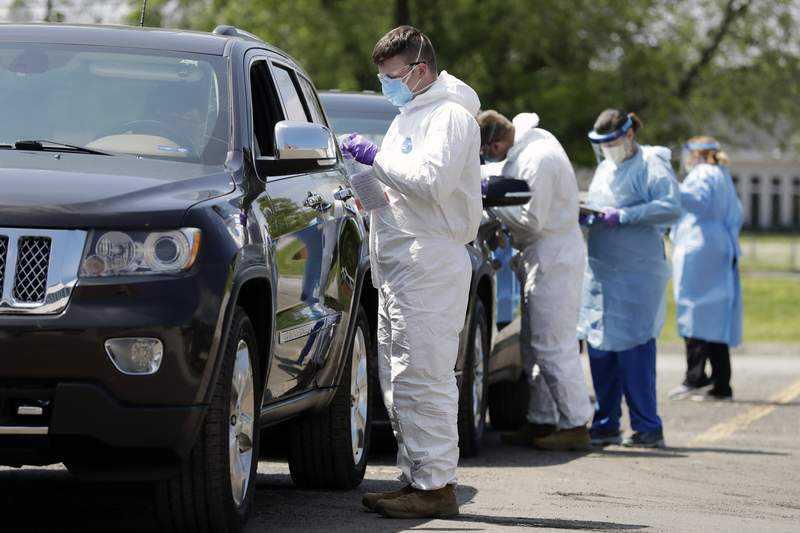 FILE - In this Saturday, April 18, 2020, file photo, workers administer tests at a drive-through COVID-19 testing location in Franklin, Tenn. Testing is critical to controlling the coronavirus and eventually easing restrictions that have halted daily life for most Americans. (AP Photo/Mark Humphrey, File)