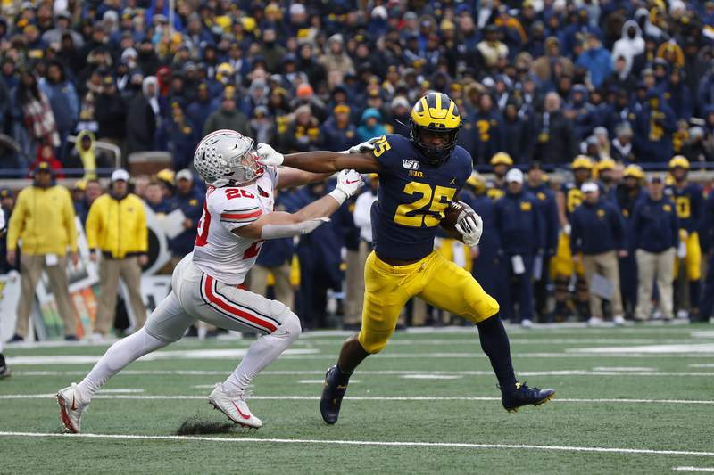 Michigan running back Hassan Haskins (25) stiff arms Ohio State linebacker Pete Werner (20) while scoring a 2-point conversion in the second half of an NCAA college football game in Ann Arbor, Mich., Saturday, Nov. 30, 2019.