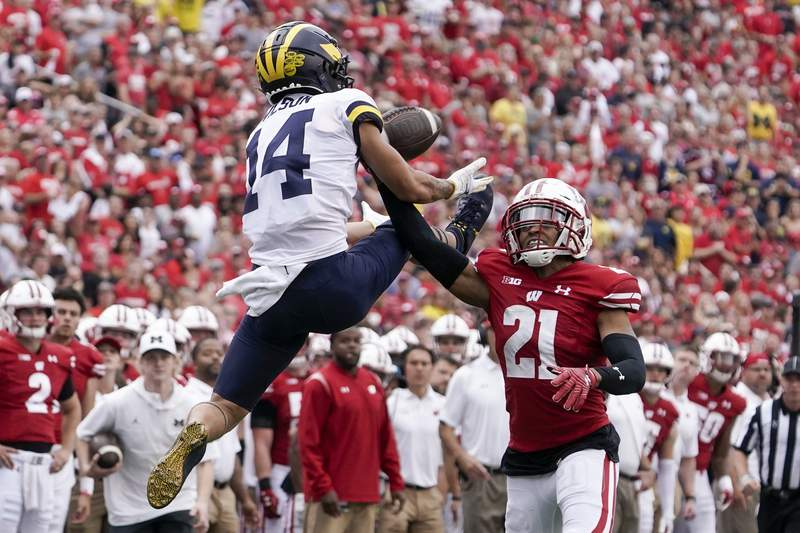 Michigan's Roman Wilson catches a pass in front of Wisconsin's Caesar Williams during the second half of an NCAA college football game Saturday, Oct. 2, 2021, in Madison, Wis. (AP Photo/Morry Gash)