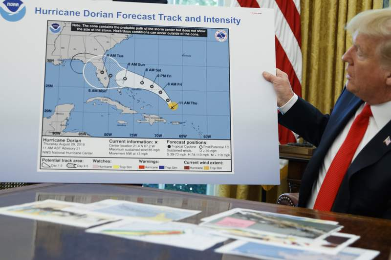 FILE - In this Sept. 4, 2019, file photo, President Donald Trump holds a chart as he talks with reporters after receiving a briefing on Hurricane Dorian in the Oval Office of the White House in Washington. Political pressure from the White House and a series of crazy in the middle of the night texts, emails and phone calls caused top federal weather officials to wrongly admonish a weather office for a tweet that contradicted President Trump about Hurricane Dorian in 2019, an inspector general report issued Thursday, July 9, 2020, found.  (AP Photo/Evan Vucci. File)