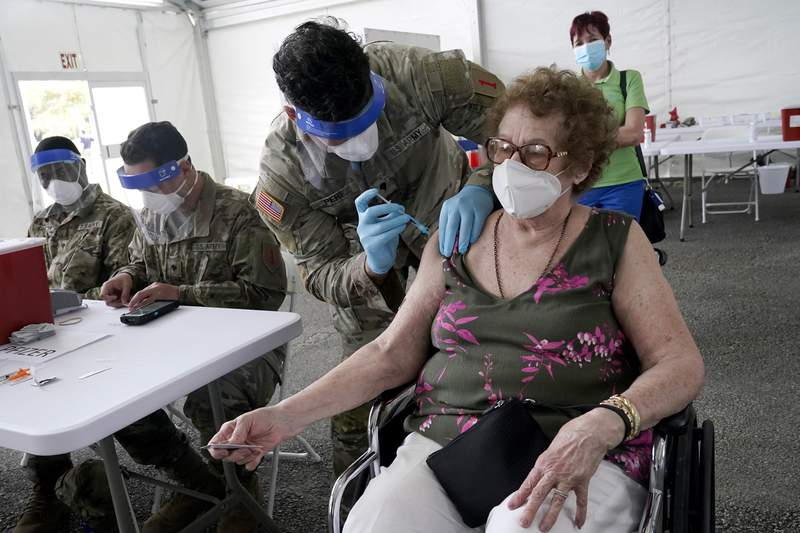 FILE - In this March 3, 2021, file photo, In this Loida Mendez, 86, gets the first dose of the Pfizer COVID-19 vaccine from U.S. Army medic Luis Perez, at a FEMA vaccination site at Miami Dade College in North Miami, Fla. Thousands of older Americans are spending hours online or enlisting their grandchildren's help to sign up for a COVID-19 vaccine. An untold number of older people are getting left behind in the desperate dash for shots because they are too frail, overwhelmed, isolated or poor to navigate a system that favors healthier individuals with more resources. (AP Photo/Marta Lavandier, File)
