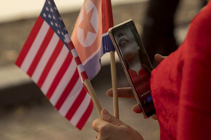 FILE - In this Feb. 27, 2019, file photo a woman holds American and North Korean flags as she walks along Sword Lake in Hanoi, Vietnam. The Biden administration has extended for one year a Trump-era ban on the use of U.S. passports for travel to North Korea.  The ban had first been imposed by former Secretary of State Rex Tillerson in 2017 after the death of American student Otto Warmbier who suffered grievous injuries while in North Korean custody. It has been extended annually ever since. (AP Photo/Andrew Harnik, File)