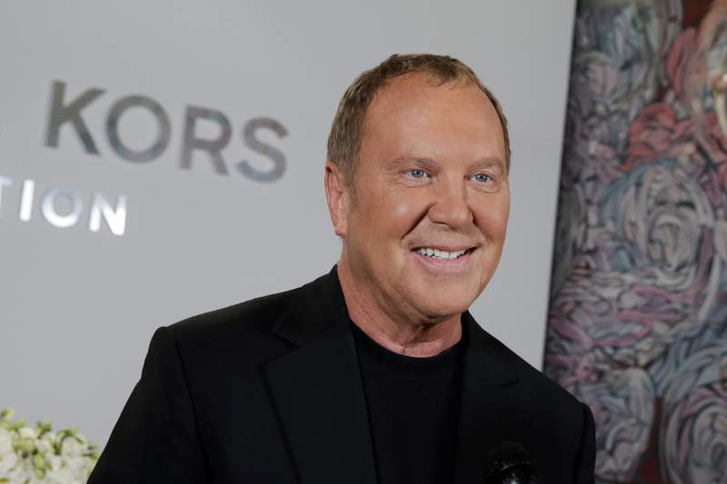 FILE - Designer Michael Kors appears before his Spring 2017 collection is modeled during Fashion Week, in New York, on Sept. 14, 2016. Kors loves fashion, but he also loves the Broadway theater. He celebrated that love as he marked his 40th anniversary as a designer this week, with a show that showcased the razzle-dazzle of Broadway. His models sashayed down a runway that was actually West 45th street, in the heart of Manhattans still-shuttered theater district. (AP Photo/Richard Drew, File)