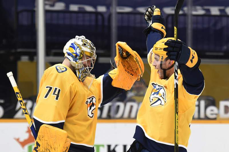 Nashville Predators goaltender Juuse Saros (74) celebrates with defenseman Jeremy Davies (38) after the Predators defeated the Tampa Bay Lightning in an NHL hockey game Tuesday, April 13, 2021, in Nashville, Tenn. (AP Photo/Mark Zaleski)