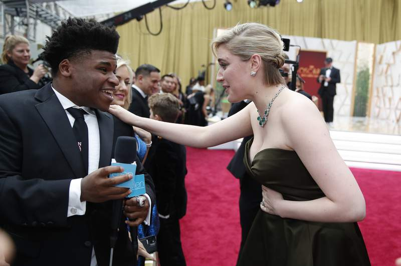 FILE - In this Feb. 9, 2020 file photo, Greta Gerwig, right, talks to Jerry Harris on the red carpet at the Oscars at the Dolby Theatre in Los Angeles. Harris, the star of the Netflix documentary series Cheer, was arrested Thursday, Sept. 17 on child pornography charges. (AP Photo/John Locher File)