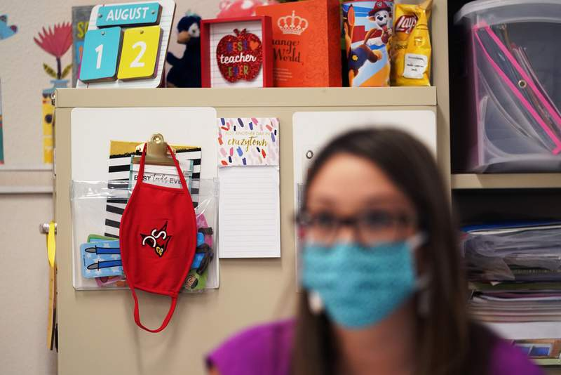 Wearing a mask to protect against the spread of COVID-19, kindergarten teacher Amber Ximenz prepares her classroom at Southside Independent School District, Thursday, Aug. 13, 2020, in San Antonio. (AP Photo/Eric Gay)