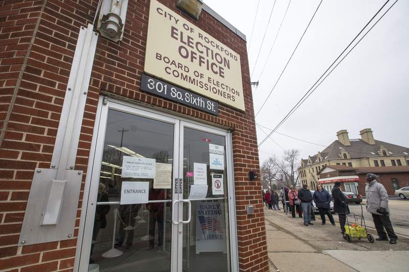 People stand in line to vote at the City of Rockford Election Office on Monday, March 16, 2020, in Rockford, Ill. Gov. J.B. Pritzker and state officials said Monday that despite restaurants, bars and other businesses being ordered closed, the Illinois Primary will be held as planned. (Scott P. Yates/Rockford Register Star via AP)