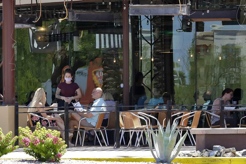 Guests dine in-house at a restaurant Wednesday, May 13, 2020, in Phoenix. Arizona Gov. Doug Ducey has allowed the reopening of restaurants in-house dining, gyms, spas and community swimming pools since Monday. Professional sports leagues will be allowed to begin practicing in Arizona after the state's current stay-at-home order expires Friday. (AP Photo/Matt York)