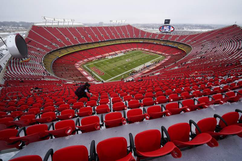A worker cleans seats in Arrowhead Stadium before an NFL football game between the Kansas City Chiefs and the Los Angeles Chargers, Sunday, Jan. 3, 2021, in Kansas City. (AP Photo/Charlie Riedel)