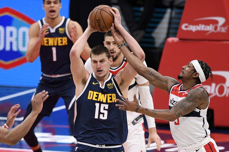 Washington Wizards guard Bradley Beal (3) reaches for the ball against Denver Nuggets center Nikola Jokic (15) during the first half of an NBA basketball game, Wednesday, Feb. 17, 2021, in Washington. (AP Photo/Nick Wass)