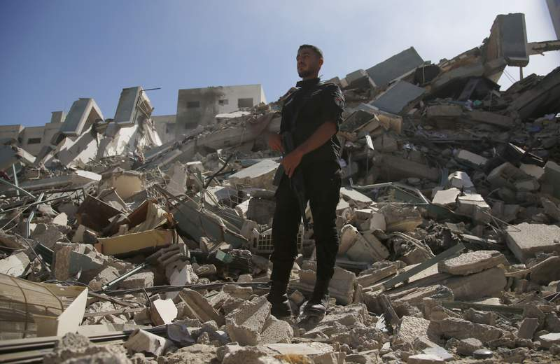 A man stands on rubble from a building housing AP office and other media in Gaza City that was destroyed after Israeli warplanes demolished it, Saturday, May 15, 2021.  The airstrike Saturday came roughly an hour after the Israeli military ordered people to evacuate the building. There was no immediate explanation for why the building was targeted. (AP Photo/Hatem Moussa)