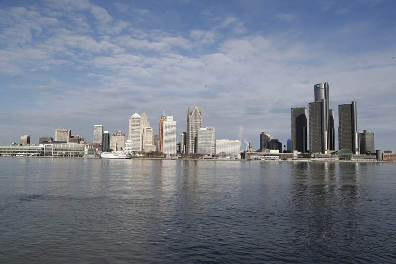 In this Jan. 11, 2019 photo, the Detroit skyline is seen from Windsor, Ont. Detroit's fiscal future faces a new daunting foe in the coronavirus.  Detroit Mayor Mike Duggan on Tuesday, April 14, 2020, announced some layoffs, pay cuts for other employees and and a reduction in some services. He warned that Detroit could be subject to a return to state oversight if action isn't taken quickly. (AP Photo/Carlos Osorio)
