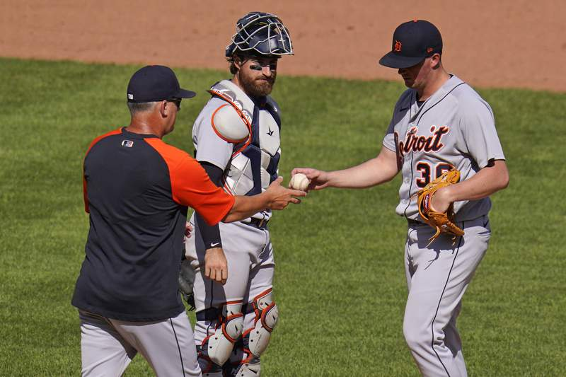 Detroit Tigers relief pitcher Kyle Funkhouser, right, hands the ball to manager A.J. Hinch, left, as catcher Eric Haase looks on during a pitching change in the seventh inning of a baseball game against the Pittsburgh Pirates in Pittsburgh, Monday, Sept. 6, 2021.