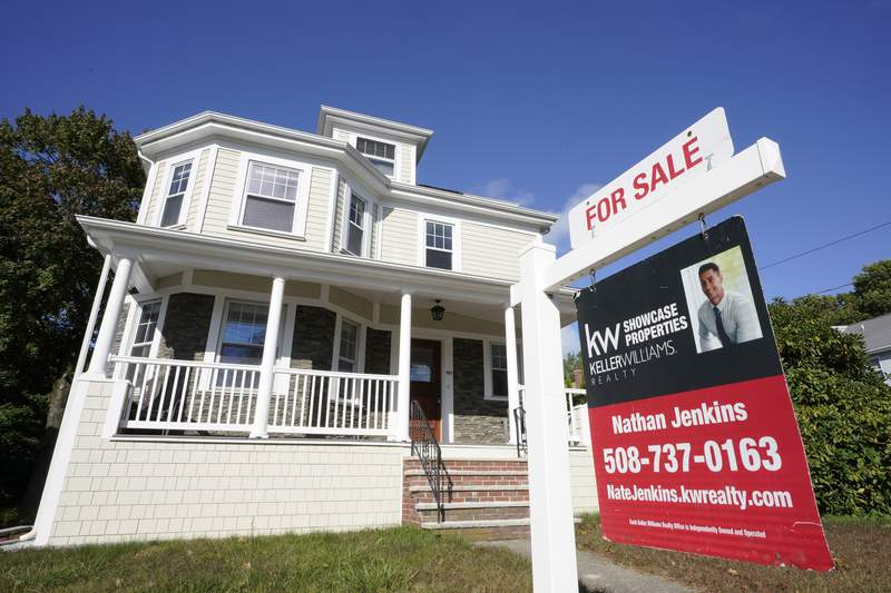 A for sale sign stands in front of a house, Tuesday, Oct. 6, 2020, in Westwood, Mass. U.S. long-term mortgage rates slipped this week as the key 30-year loan marked a new all-time low for the 11th time this year. Home loan rates have notched a year-long decline amid economic anxiety in the recession set off by the coronavirus pandemic. (AP Photo/Steven Senne)