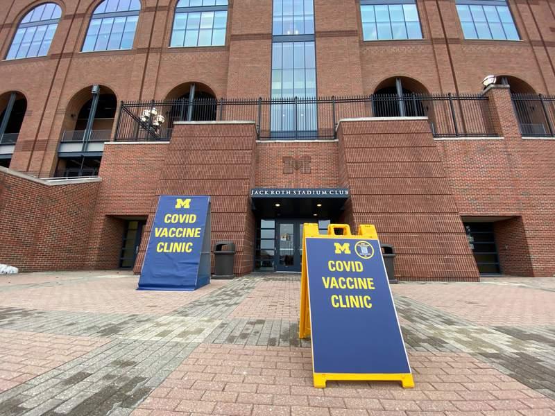 Signs guide individuals to Michigan Medicine's COVID Vaccine Clinic at the Jack Roth Stadium Club at Michigan Stadium on Dec. 31, 2020.