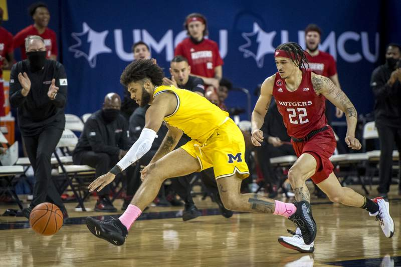 Isaiah Livers #2 of the Michigan Wolverines and Caleb McConnell #22 of the Rutgers Scarlet Knights go for a loose ball at Crisler Arena on February 18, 2021 in Ann Arbor, Michigan.