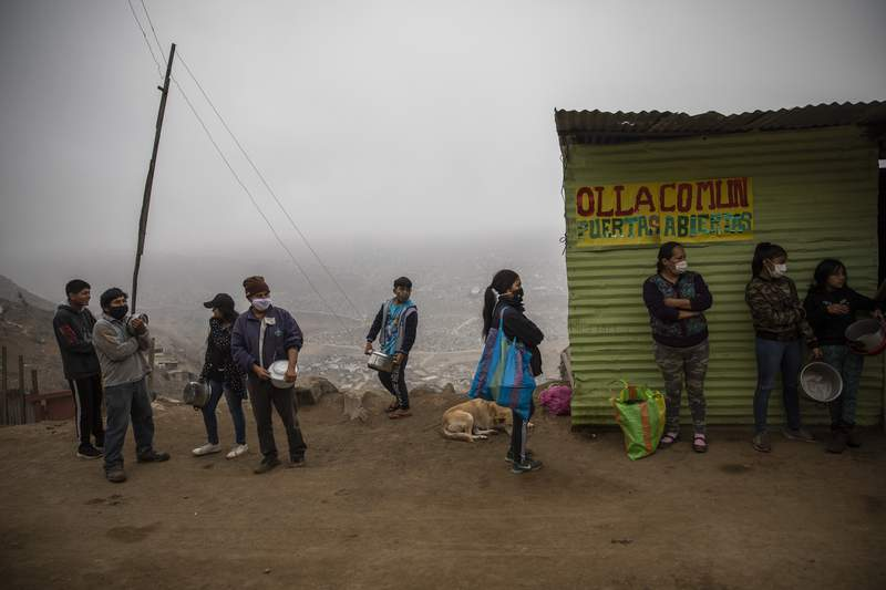 """Residents wait in line at a """"community pot,"""" in the Nueva Esperanza neighborhood of Lima, Peru, Wednesday June 17, 2020. For many residents the """"community pot"""" is their only defense against a hunger that's become a constant feature of life amid the new coronavirus pandemic. (AP Photo/Rodrigo Abd)"""