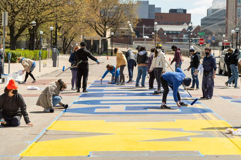 The University of Michigan commencement mural honors the U-M Class of 2021 and was painted by 29 undergraduate students from the U-M Penny W. Stamps School of Art & Design. It is located on the street outside of the Rackham Graduate School (915 E. Washington Street), between Thayer and Fletcher Streets.