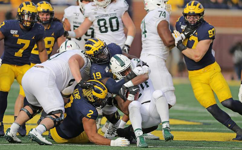 Kwity Paye #19 of the Michigan Wolverines makes the stop on Elijah Collins #24 of the Michigan State Spartans during the second quarter of the game at Michigan Stadium on November 16, 2019 in Ann Arbor, Michigan. Michigan defeated Michigan State 40-10.