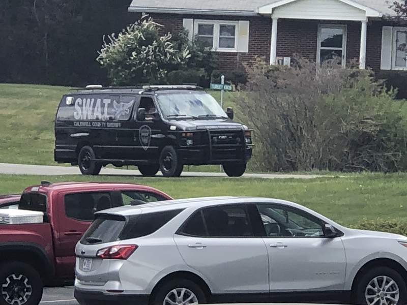 In this photo provided by WJZY, a tactical van from Caldwell County, North Carolina, sits on stand-by at a staging area in Boone, N.C., on Wednesday, April 28, 2021. Law enforcement agencies responded to a standoff in Boone in which two Watauga County sheriffs deputies were shot and wounded. (Morgan Frances/WJZY via AP)