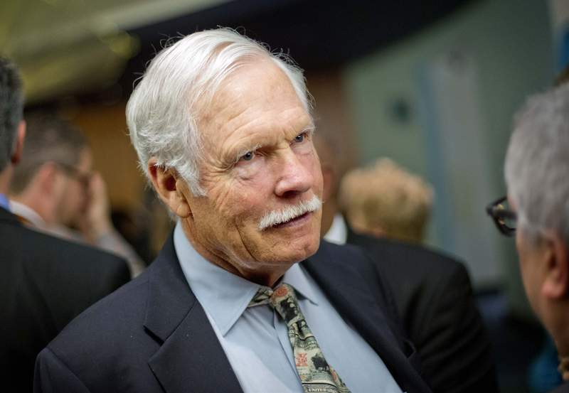 FILE - In this Dec. 6, 2013, file photo, Ted Turner talks with guests at the Captain Planet Foundation benefit gala in Atlanta. Media mogul and billionaire bison rancher Turner is donating an 80,000-acre ranch he owns in western Nebraska to his own nonprofit agriculture ecosystem research institute and says he might do the same with four other ranches in Nebraska's Sand Hills. But he'll continue to pay taxes on the land, much to the relief of local officials and Nebraska leaders, the Omaha World-Herald reported Thursday, July 8, 2021. (AP Photo/David Goldman, File)