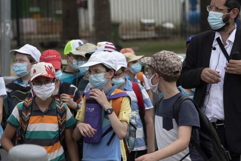 File---File picture taken July 6, 2020 shows Israeli school children wearing face masks to help prevent the spread of the coronavirus as they walk in Tel Aviv, Israel. As Germanys 16 states start sending millions of children back to school in the middle of the global coronavirus pandemic, those used to the countrys famous Ordnung are instead looking at uncertainty, with a hodgepodge of regional regulations that officials acknowledge may or may not work. (AP Photo/Sebastian Scheiner,File)